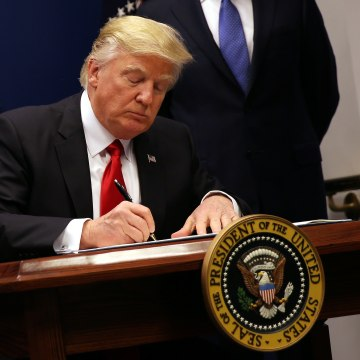 Image: U.S. President Donald Trump signs an executive order to impose tighter vetting of travelers entering the United States, at the Pentagon in Washington