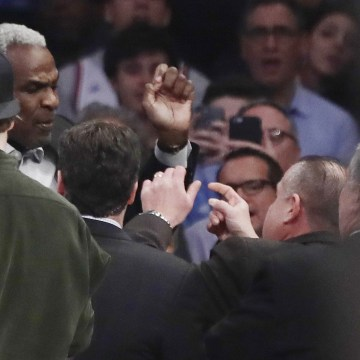 Image: Charles Oakley exchanges words with a security guard during the first half of an NBA basketball game