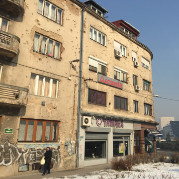Image: Bullet holes and shelling damage still scar a building in Sarajevo