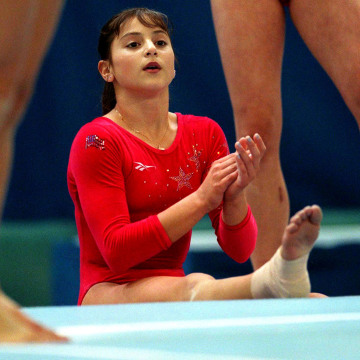 Image: Dominique Moceanu, a member of the American gymnastics team, looks on during a practice in the Malley hall in Lausanne, Aug. 29, 1997.