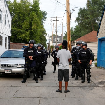 Image: Police in riot gear assemble in an alley after disturbances following the police shooting of a man in Milwaukee, Wisconsin, Aug. 15, 2016.