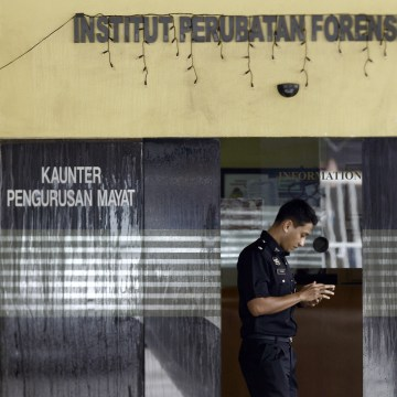 Image: A police officer checks his phone inside the forensic department at Kuala Lumpur Hospital