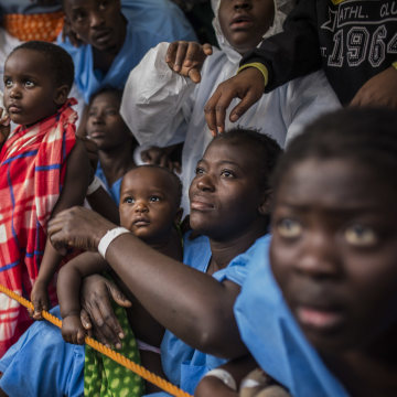 Image: African refugees and migrants wait aboard the Golfo Azurro to disembark