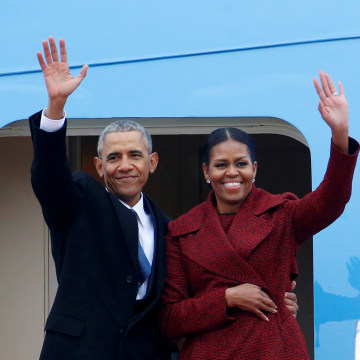 Former president Barack Obama waves with his wife Michelle as they board Special Air Mission 28000, a Boeing 747 which serves as Air Force One, at Joint Base Andrews