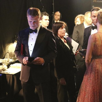Image: Brian Cullinan  holds red envelopes under his arm while using his cell phone backstage at the Oscars