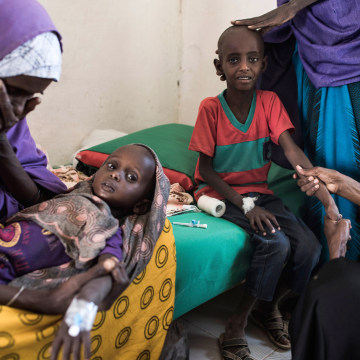 Image: Abdullahi Mohamud, 5, cries next to his mother Sahro Mohamed Mumin, 30, and brother, Abdulrahman Mahamud, 2, as a nurse struggles to find a vein for an injection at a government run health clinic in Shada, Somalia.