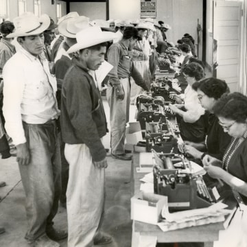 Image:  Temporary clerks completing the short-term labor contracts and identification cards.