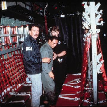Image: U.S. Drug Enforcement Agents help Manuel Antonio Noriega into a C-130 transport plane en route from Panama City to Miami