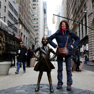 Image: A woman poses next to a statue of a girl facing the Wall St. Bull, as part of a campaign by U.S. fund manager State Street to push companies to put women on their boards, in the financial district in New York