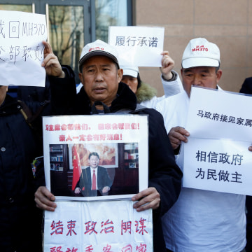Image: Relatives of missing passengers hold up placards Wednesday outside the foreign ministry in Beijing, China.