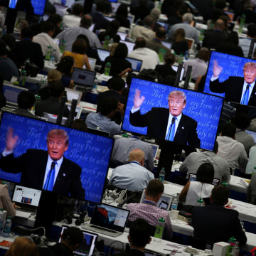 Image: Trump appears on television screens in the media room during the first presidential debate
