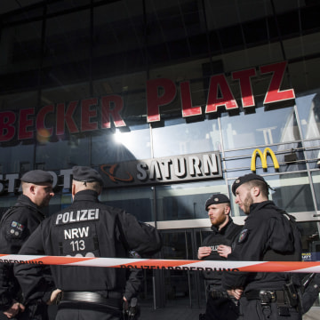 Image: Policemen guard the front of a shopping mall