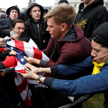 "Counter-demonstrators (L) and supporters (R) of U.S. President Donald Trump fight for a U.S. flag during a ""People 4 Trump"" rally in Berkeley, California"