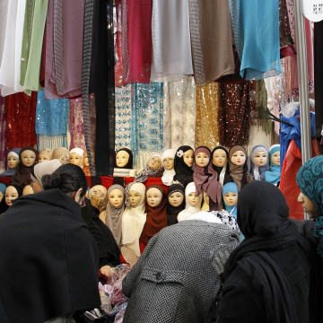 Image: Women look at veils on display