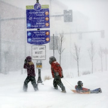 Image: People make their way through the snow-filled streets of Pittsfield, Mass.