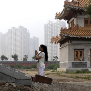 Image: A woman prays in Tianjin