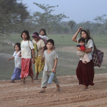 Image: Tsimane indigenous people walk down a road heading to Yucomo, Bolivia