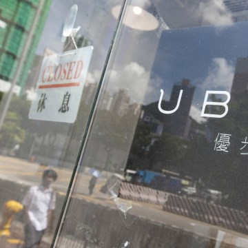 Image: Buildings are reflected in a window of an office of the taxi mobile app service Uber.