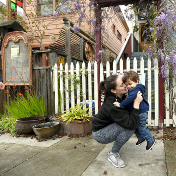 Image: Joy Ashe holds her son Zion Ashe, 1, outside their home in Emeryville