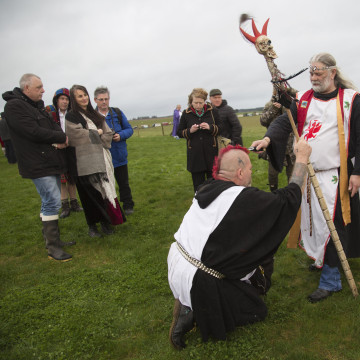 Image: King Arthur Uther Pendragon knights a fellow druid at Stonehenge