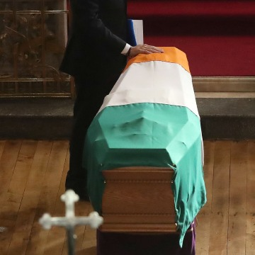 Image: Former President Bill Clinton touches Martin McGuinness's coffin