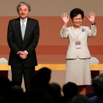 Image: Carrie Lam waves after she won the election for Hong Kong's next Chief Executive as other candidates John Tsang and Woo Kwok-hing stand next to her in Hong Kong