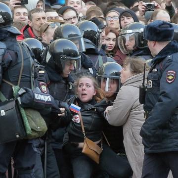 Image: Russian riot policemen detain a demonstrator.