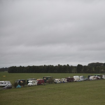 Image: A line of RVs and trailers parked outside the entrance of Stonehenge