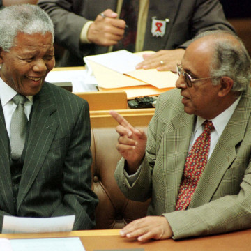 Image: President Nelson Mandela talks to fellow veteran politician Ahmed Kathrada before Mandela's address to Parliament in Cape Town March 2, 1999.