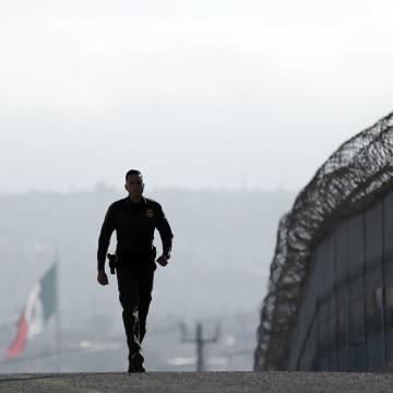 Image: A Border Patrol agent walks near a fence in San Diego
