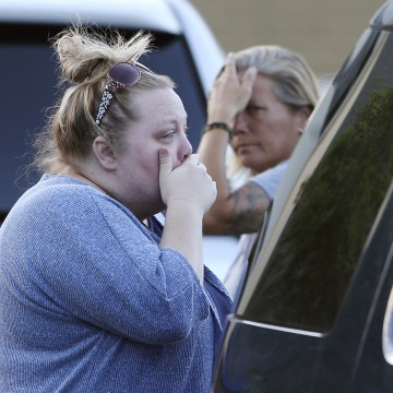 Image: Women react outside the First Baptist Church after several church members died in a crash