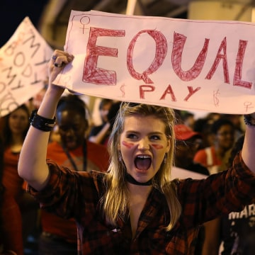 """Image: A protester holds a sign that readings """"Equal Pay"""""""