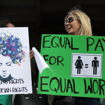 Image: Protesters hold signs during a rally to support equal pay for equal work