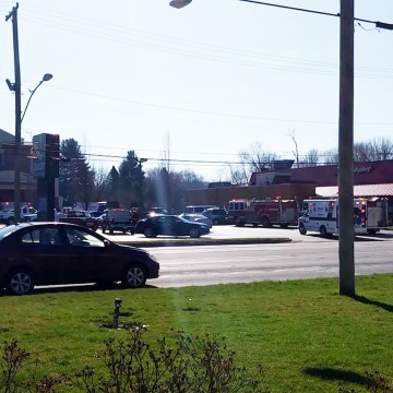 Image: Fire trucks and ambulances line the parking lot in front of a Niles, Michigan Quality Inn, where a Carbon Monoxide leak has killed at least one person and injured 12 more.