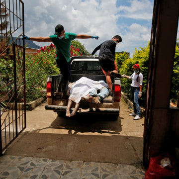Men arrive in a vehicle with bodies to be identified after flooding and mudslides caused by heavy rains in Villagarzon