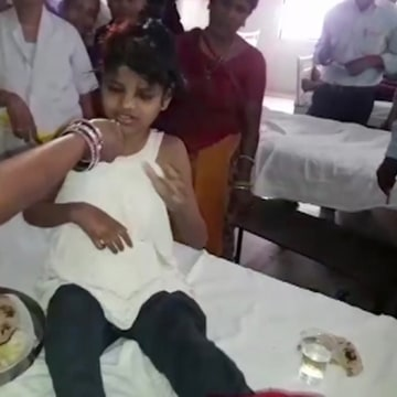 Image: A young Indian girl sits on a bed at a hospital