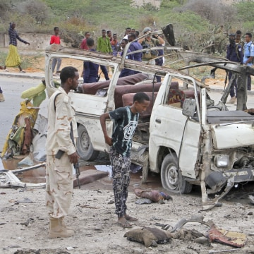 Image: A Somali soldier stands by the wreckage of a passing minibus that was destroyed in a suicide car bomb attack near the defense ministry compound in Mogadishu, Somalia, April 9, 2017.