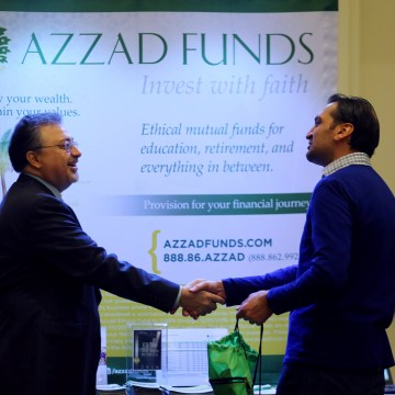 Image: Activist investor Bashar Qasem, President and CEO of Azzad Asset Management Inc, greets a client during a conference in Huntington Beach, California