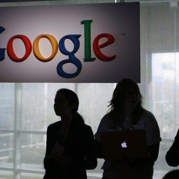 Image: People stand under a sign at Google headquarters