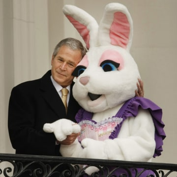 Image: President George W. Bush hugs a person dressed as the Easter bunny at the annual Easter egg roll