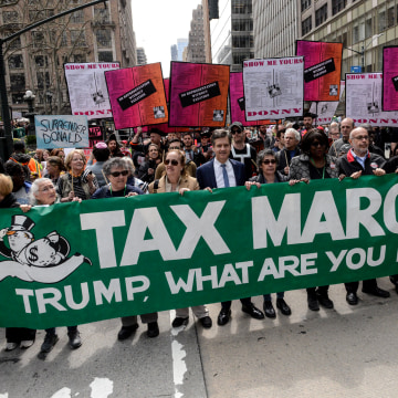 Image: People participate in a Tax Day protest on April 15, 2017 in New York City. Activists in cities across the nation are marching today to call on President Donald Trump to release his tax returns.
