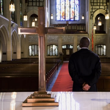 Mixed race pastor standing in front of church altar