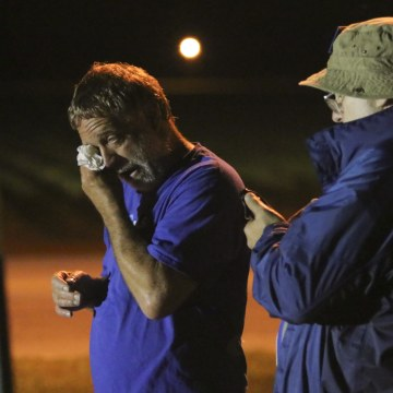 Image: Anti-death penalty supporter Randy Gardner, left, wipes away a tear moments after Abraham Bonowitz, left, reads on his phone the 11:45pm Supreme Court decision to halt the execution
