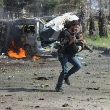 Image: Abd Alkader Habak is photographed carrying a wounded Syrian boy