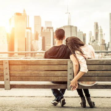 Image: A couple sits on a bench during sunset