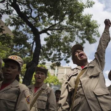 Image: A member of the Bolivarian Militia raises his fist