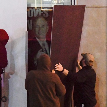 Image: Men place boards over Bill O'Reilly poster outside of the Fox News offices in Manhattan, New York