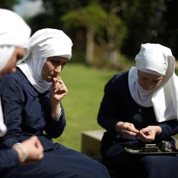 "Image: California ""weed nun"" Christine Meeusen, Desiree Calderon, who goes by the name Sister Freya, and India Delgado, who goes by the name Sister Eevee, smoke at Sisters of the Valley near Merced"