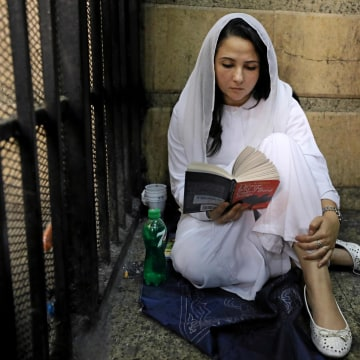 Image: Aya Hijazi, founder of a non-governmental organisation that looks after street children, sits reading a book inside a holding cell at a courthouse in Cairo