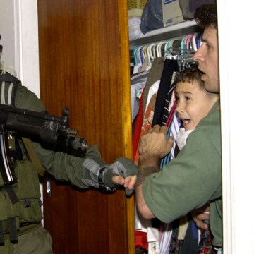 Image: Elian Gonzalez is held in a closet by Donato Dalrymple, one of the two men who rescued the Cuban boy from the ocean